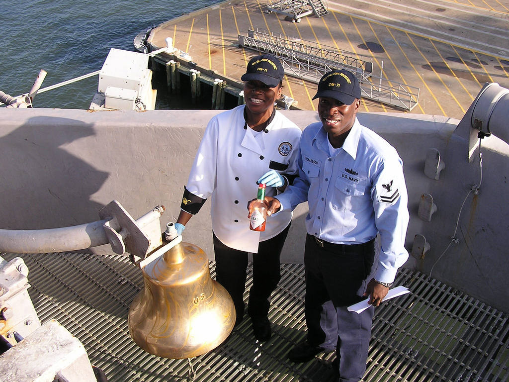 sailors cleaning the USS Theodore Roosevelt's bell with Tabasco sauce!