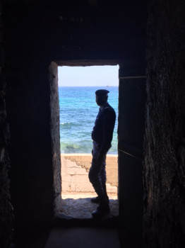 A Senegalese soldier stands in the doorway of The House of Slaves on Goree Island during OE/SE 2016. (U.S. Navy photo by Vice Adm. James Foggo, III).