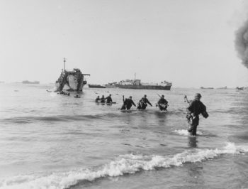 Troops with U.S. Army's Fifth Army wade ashore from HMS LCI-281 during the first day of landings, near Anzio. HMS LCI-274 is extracting from the beach, in center. Smoke at far right is from the burning USS LCI-20, victim of a German air attack. National archive photo