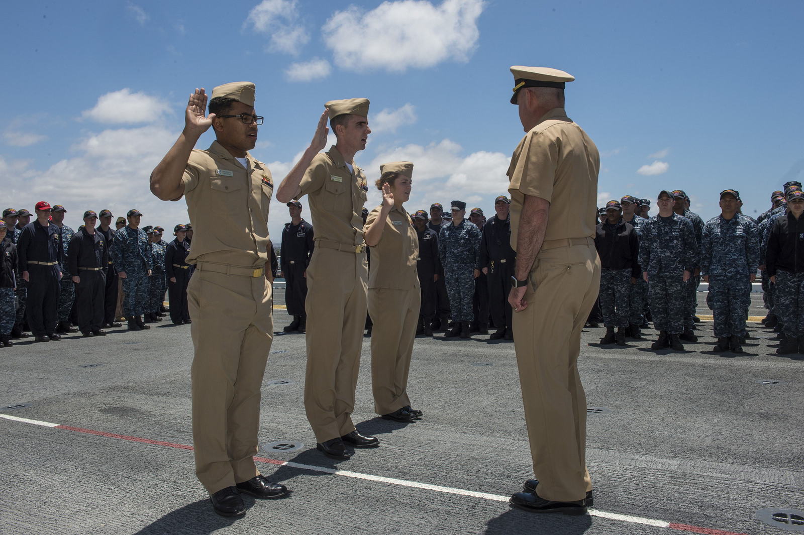 SAN DIEGO (May 23, 2016) USS Makin Island Commanding Officer Capt. Jon P. Rodgers (right) administers the Oath of Office to (left to right) Ensign Brennan Wyatt, from Greensboro, North Carolina, Ensign Derek Gilmartin, from Bakersfield, California, and Ensign Sarah Kline, from Apex, North Carolina, during their promotion to Lt. j.g. on the ship's flight deck. Makin Island is home-ported in San Diego, undergoing the basic training phase in preparation for a scheduled deployment this fall. (U.S. Navy Photo by Mass Communication Specialist Seaman Clark Lane/Released)